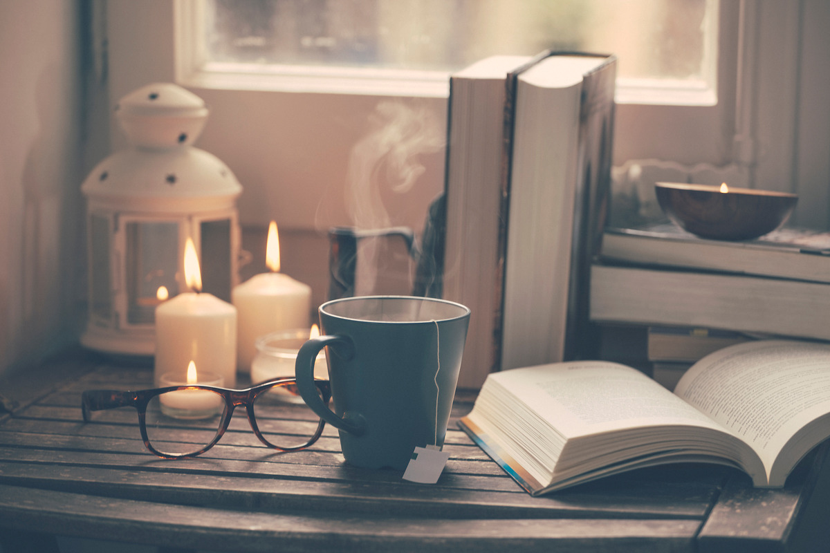 books, candles and tea on a table