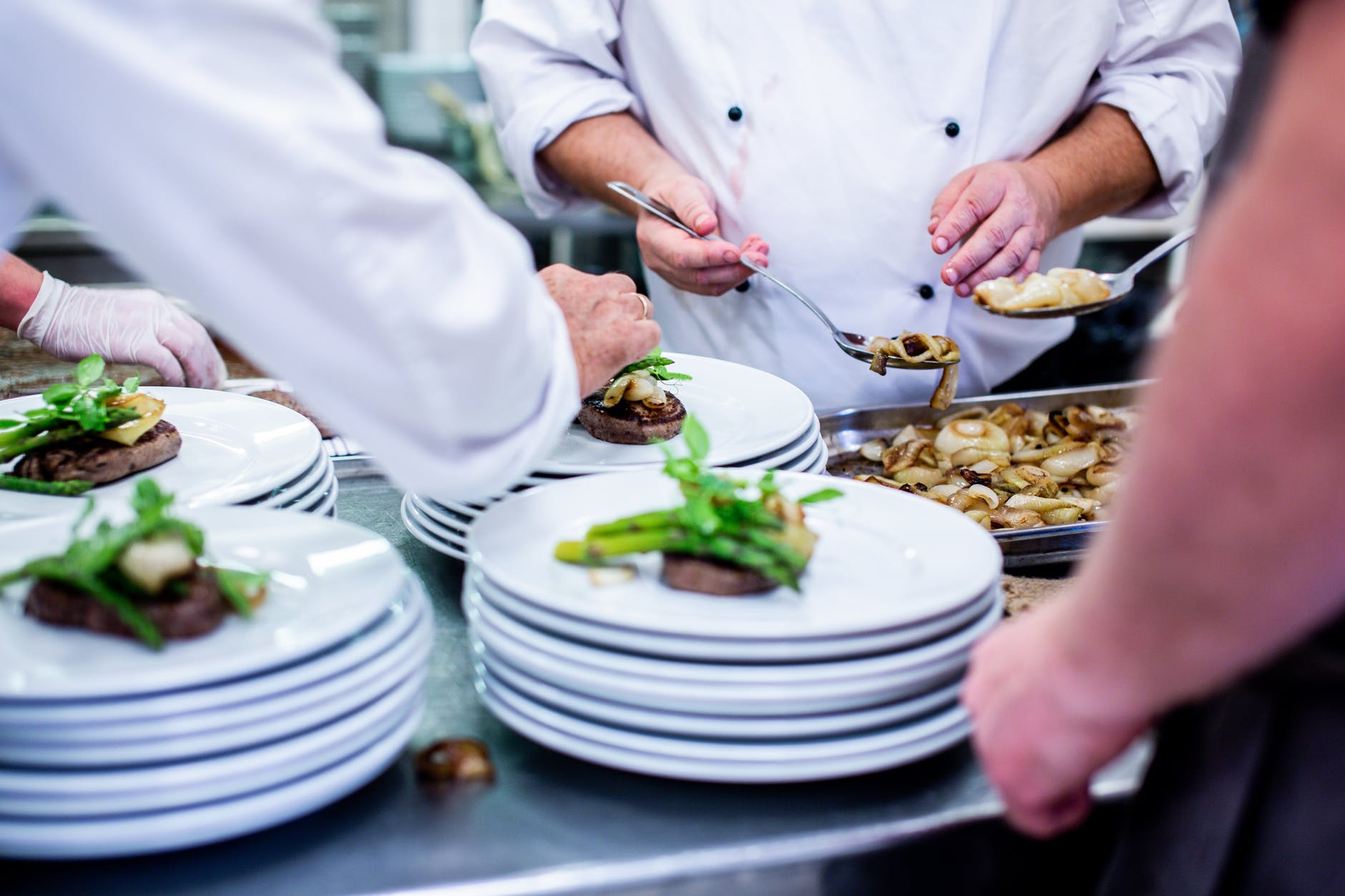 chefs preparing plates with steak and vegetables